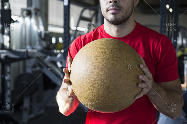 Sportsman in red t-shirt holding training ball in front while working out in gym