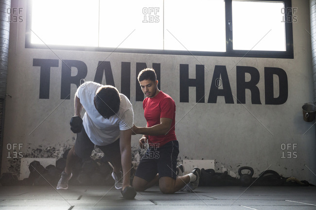 Man doing exercise with dumbbells with help of trainer in gym