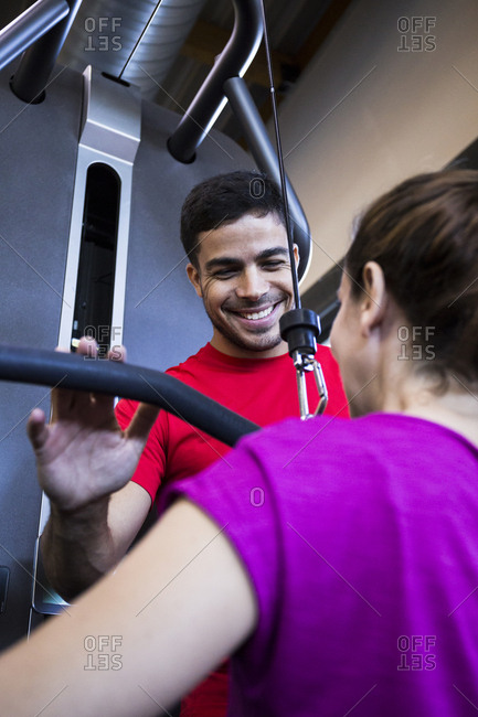 Handsome trainer in red T-shirt helping woman to use exercise machine and smiling
