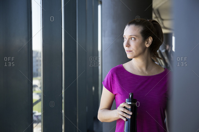 Dreaming sportswoman holding bottle of water looking away in gym window