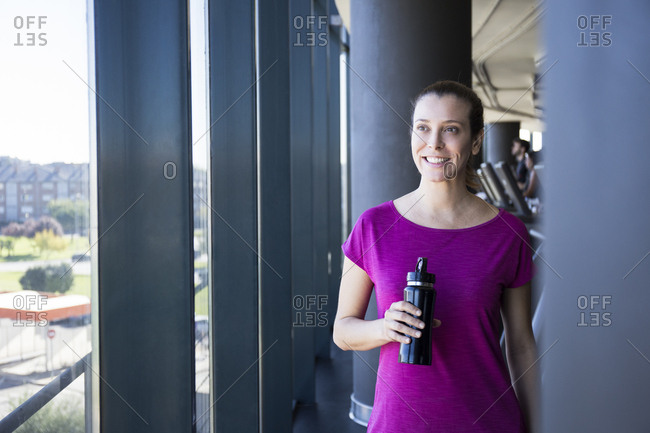 Content sportswoman looking away happily while having refreshing water in bottle