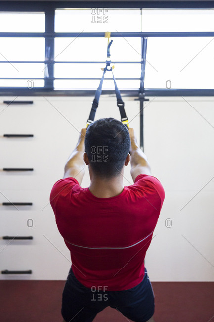 Back view of sportsman doing suspension training in gym using special ropes