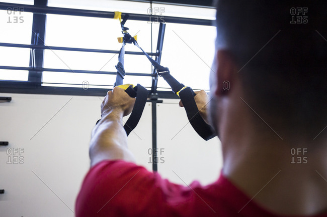 Sportsman doing suspension training in gym using special ropes
