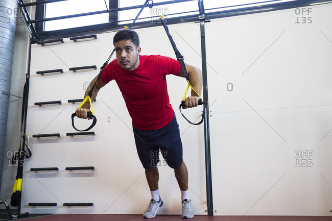 Concentrated sportsman doing suspension training hanging on straps and looking forward