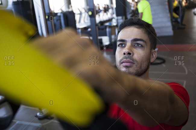 Young sportsman looking up while training suspension with special ropes in gym