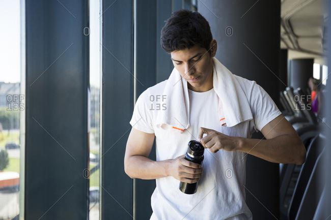 Young man in white t-shirt opening bottleof water during break