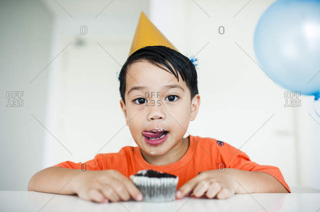 Little boy licking lips while eating a birthday cupcake