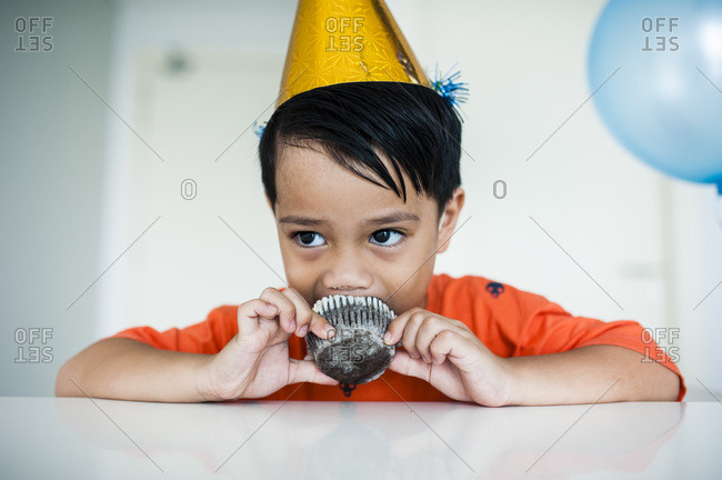 Little boy eating a birthday cupcake