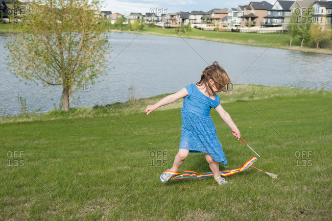 Girl twirling a rainbow ribbon beside a pond