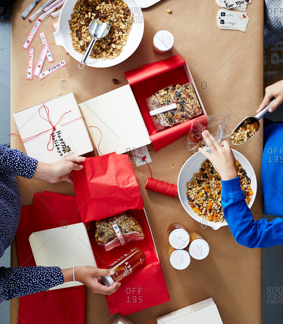 Kids packing granola and honey holiday gifts