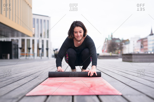 Happy woman rolling up yoga mat