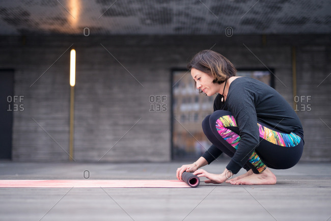 Side view of woman rolling up yoga mat
