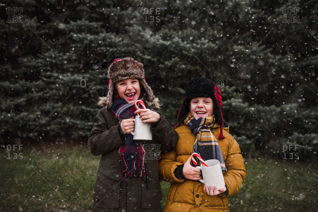 Laughing boys holding mug of hot cocoa with a candy cane