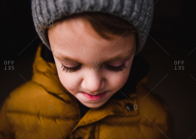Portrait of a little boy wearing yellow jacket and knit hat