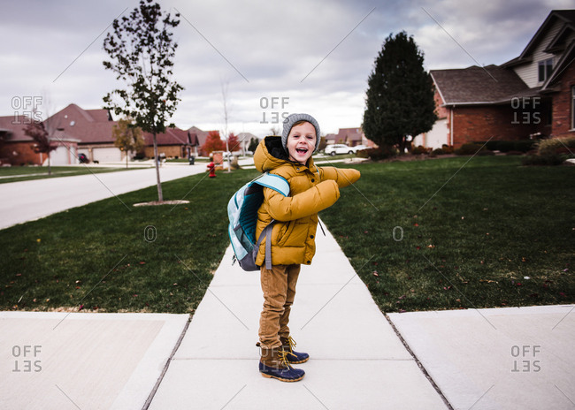Little boy waiting for bus on a chilly day