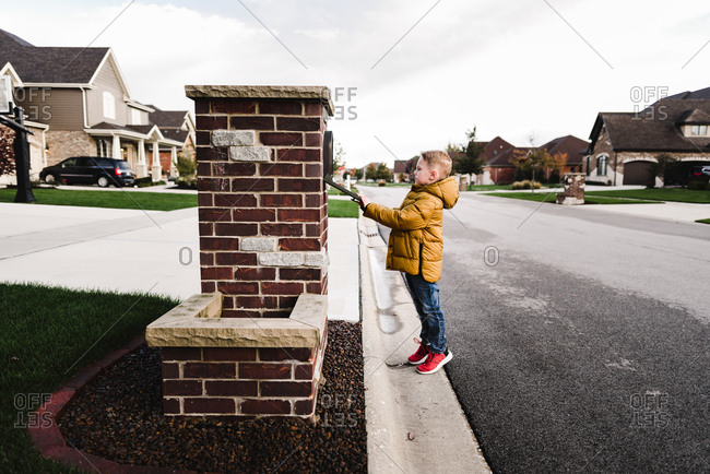 Boy looking into a mailbox