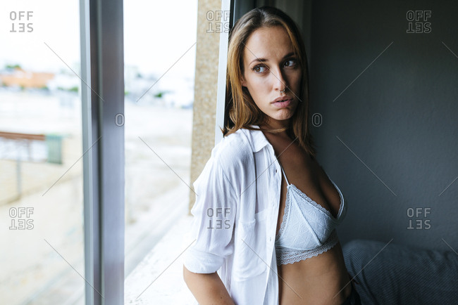 Woman looking out window with open blouse