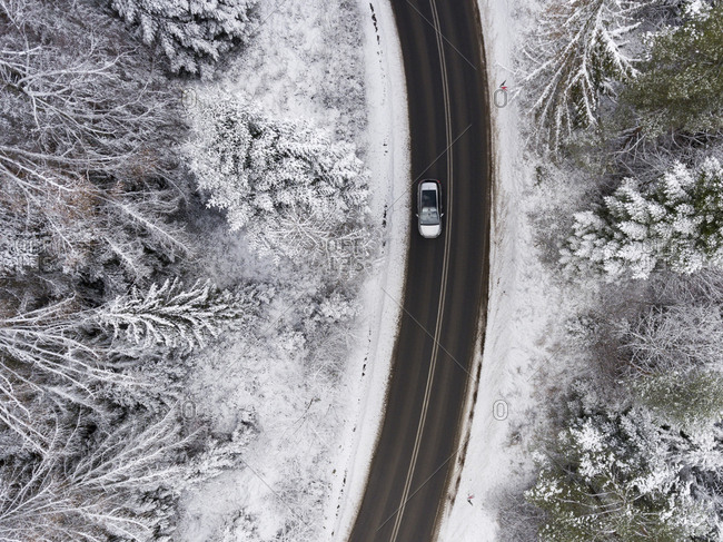 Aerial view of fresh snowfall over woods and winding road in Poland