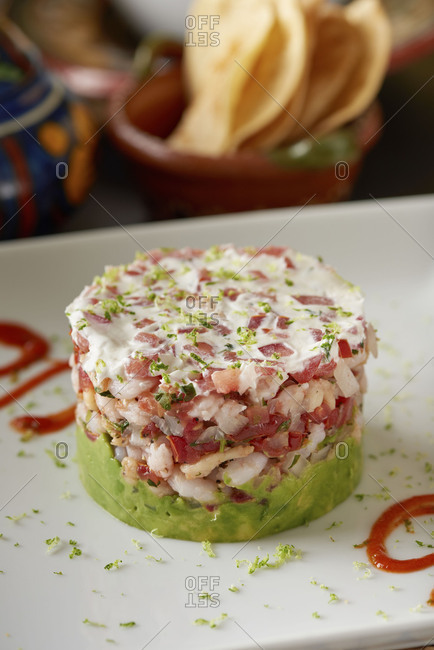 A stack of ceviche with layers of shrimp and avocado