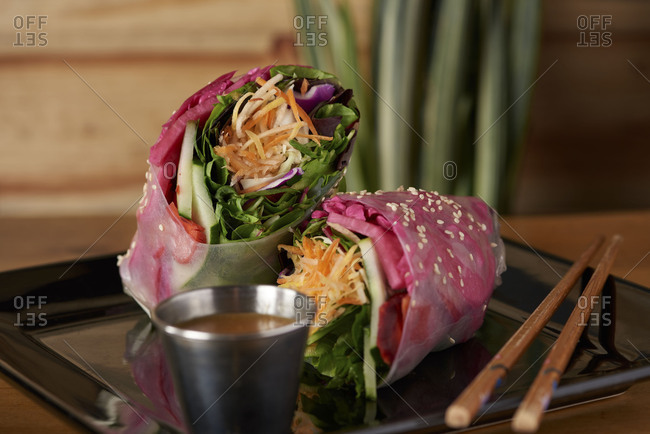 A vegan wrap served in soft rice paper including spinach, carrots, basil leaves, cabbage and served with sweet peanut sauce