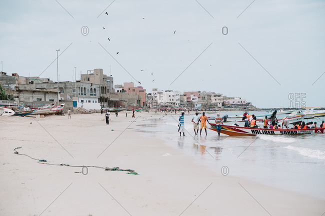 Ngor, Senegal - November 30, 2017: Side view of African people standing at vessel on sandy shore in sunny day