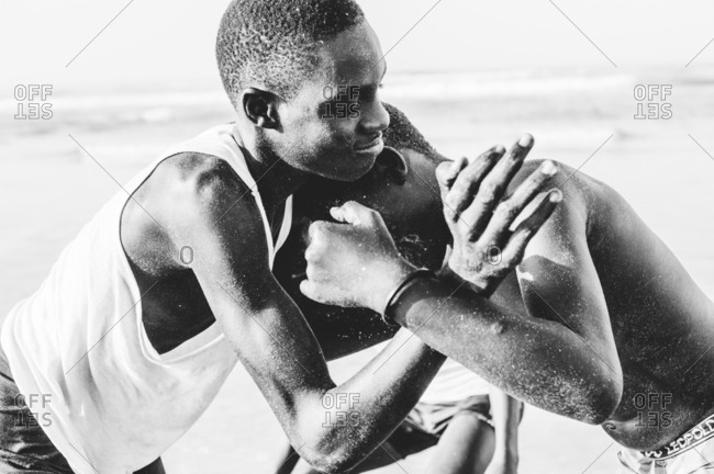 Yoff, Senegal - November 30, 2017: Black and white shot of African youngsters fighting playfully on tropical shoreline