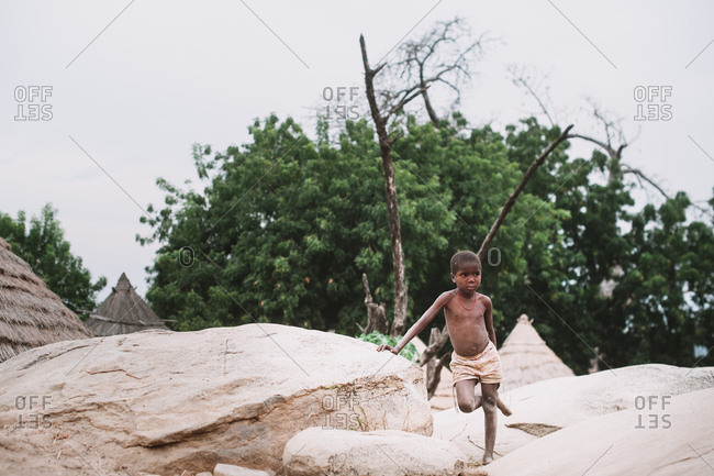 Kedougou, Senegal - November 30, 2017: Little African kid standing on rock in indigenous village on nature