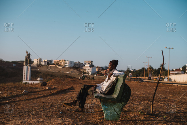 Kedougou, Senegal - November 30, 2017: African man sitting on bench in dry and dirty field on background of small town