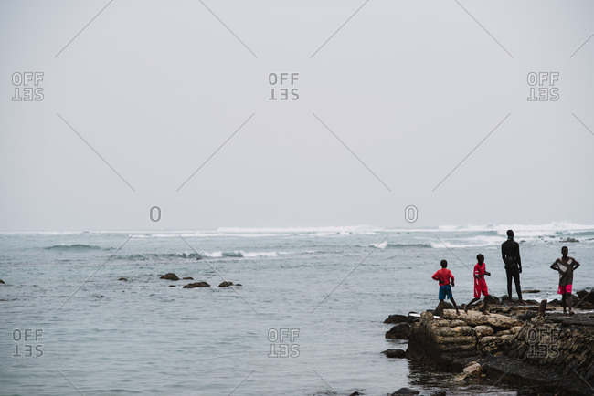 Dakar, Senegal - November 30, 2017: Group of African people standing on small rock near waving sea