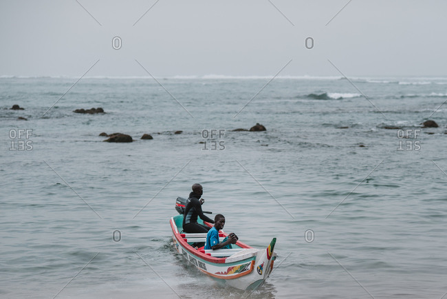 Dakar, Senegal - November 30, 2017: Two African men boating in waving sea on dull day