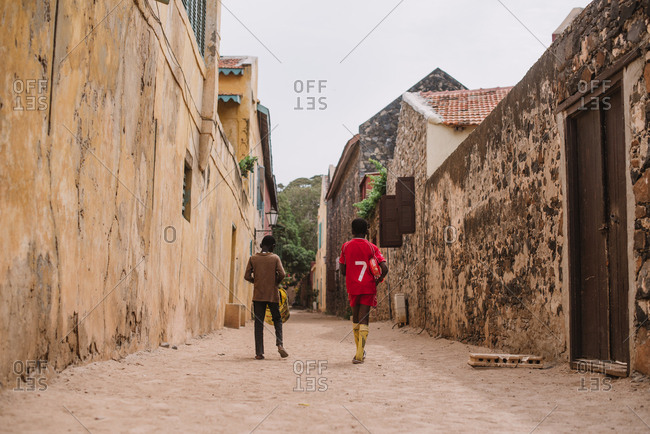 Dakar, Senegal - November 30, 2017: Two unrecognizable African boys walking along street in small African town