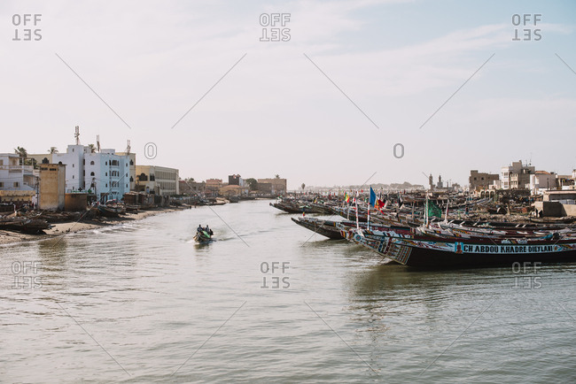 Dakar, Senegal - November 30, 2017: View of sailing boats moored on river of underdeveloped city in bright sunlight