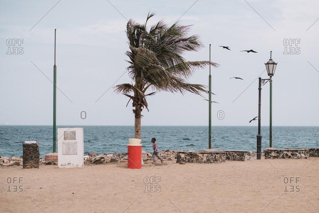 Dakar, Senegal - November 30, 2017: Little African boy running near sea on windy day