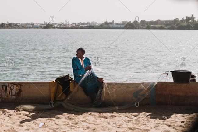Dakar, Senegal - November 30, 2017: Black man with fishing net on concrete fence of city embankment in bright sunlight