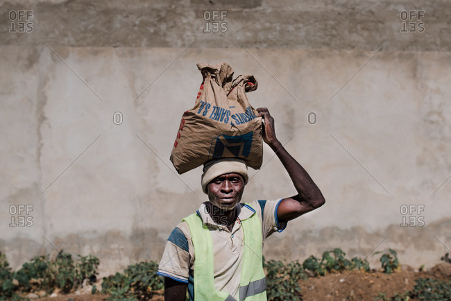 Dakar, Senegal - November 30, 2017: Senior African man carrying bag of dry substance while working on site and looking at camera