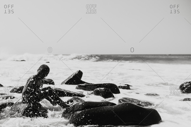 Dakar, Senegal - November 30, 2017: Black and white shot of laughing African child relaxing on rocks of coastline in drops of waves