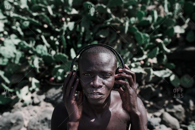 Dakar, Senegal - November 30, 2017: Portrait of African impressed man listening to music in headphones and looking at camera
