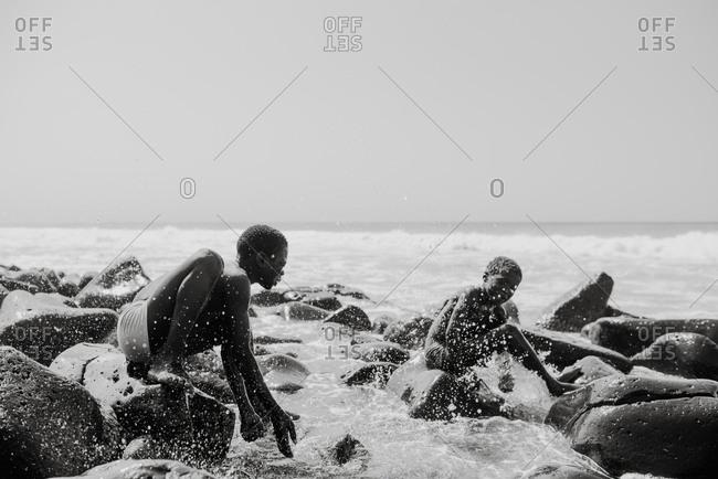 Dakar, Senegal - November 30, 2017: Cheerful black kid on rock in waves