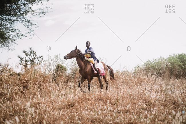 Dakar, Senegal - November 30, 2017: African confident boy riding horse in dry grass of rural field