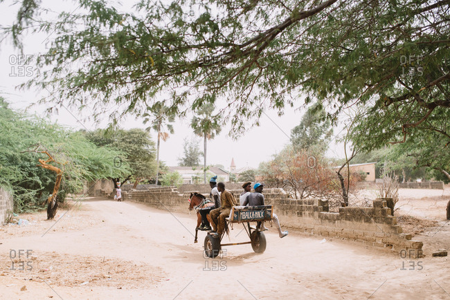 Dakar, Senegal - November 30, 2017: Group of black children on cart harnessed with horse riding down road in poor village