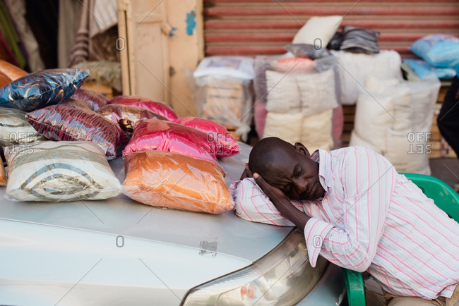 Dakar, Senegal - November 30, 2017: Tired African man sleeping on car trunk while trading on market in small African town