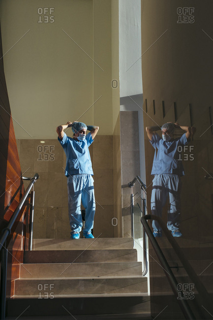 Man in uniform looking out of hospital window after operation looking tired
