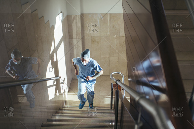 From above shot of surgeon in uniform walking up stairway in modern hospital