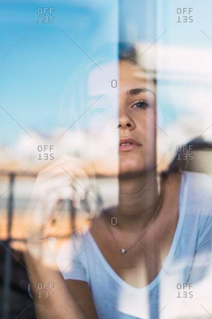 Beautiful young woman through glass