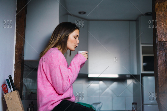 Casual woman posing at home with coffee