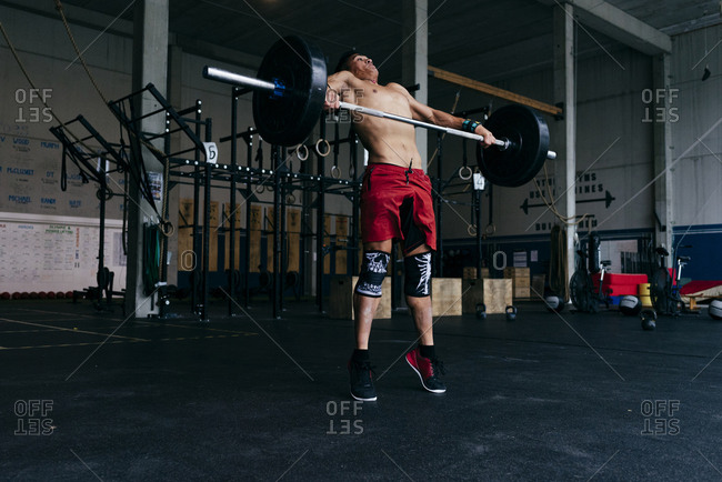 Sportsman with heavy barbell n gym