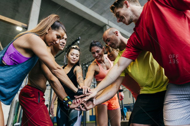 Group of confident sportive men and women stacking hands in gym