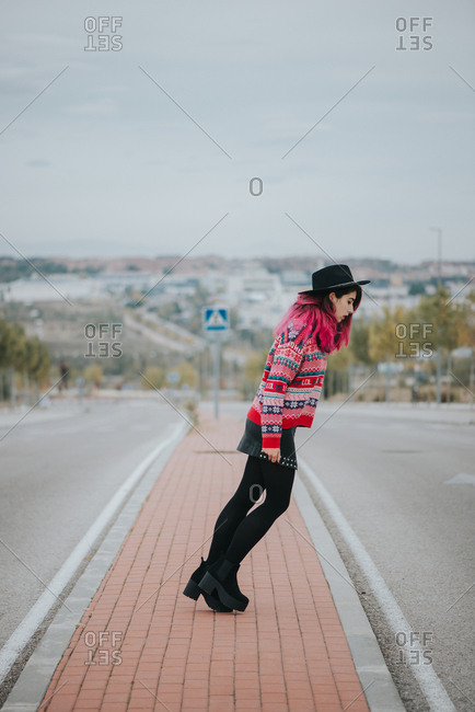 Pretty young woman standing near road and doing Michael Jackson stance