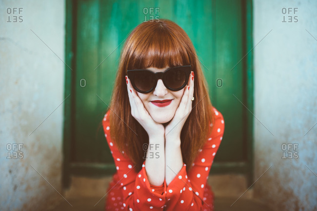 Portrait of redhead woman in elegant sunglasses leaning on hands looking at camera
