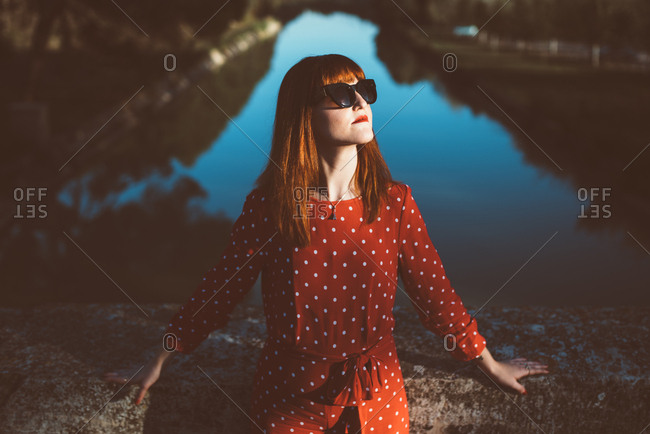 Young redhead woman in red clothing and sunglasses posing confidently in sunlight on nature